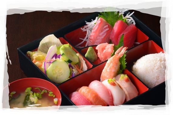 Bento box with miso soup, sushi, salad and rice